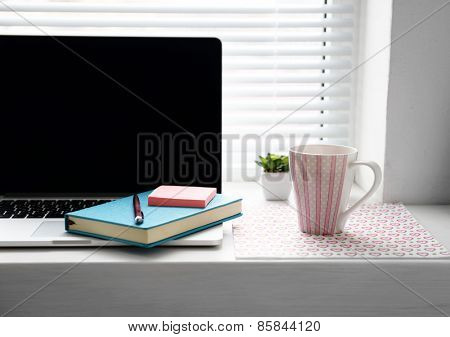 Laptop, notebook on windowsill. Working place concept