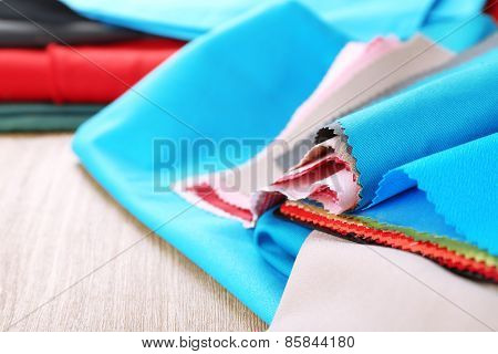 Colorful fabric samples on wooden table background