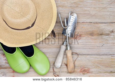 Hat, Gardening Shoes And Tools On Wood Background