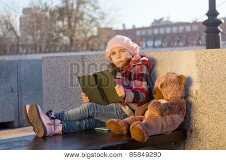 Little Girl Sits On A Bench  With The Book And A Toy Bear