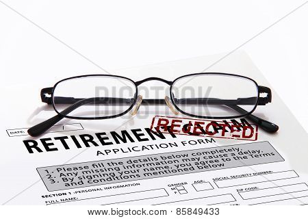 Retirement claim form with red rejected rubber stamp and glasses