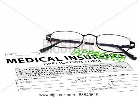 Medical insurance application form with green approved rubber stamp