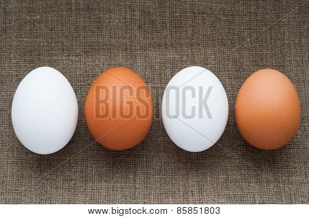 Different color eggs in line on hessian linen fabric cloth texture background