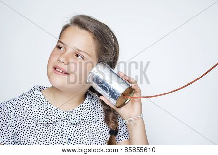 Smiling child using a can as telephone against gray background