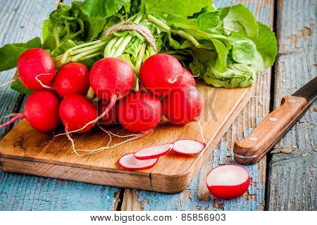 bright Fresh Organic Radishes With Slices On Cutting Board