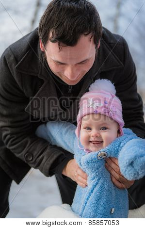 Smiling baby on father hands. Happy infant girl while Hiking in winter