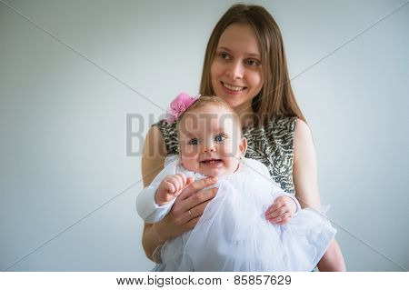 Beautiful young mother and her cute daughter in white dress