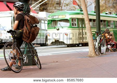 Vintage Street Car Passes Waiting Cyclist In San Francisco