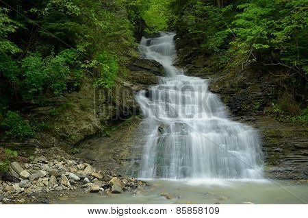 Spring landscape with the river. Beautiful waterfall in the mountains