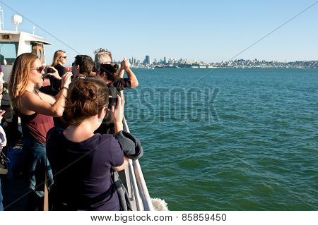Tourists Take Smart Phone Photos On Ferry In San Francisco