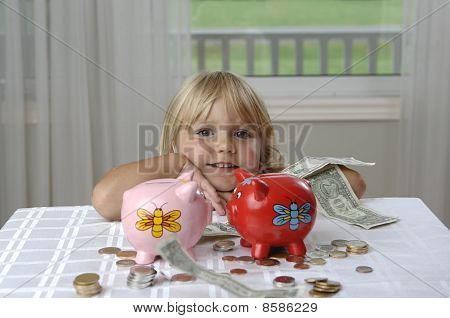 Preschool Girl And Piggy Banks