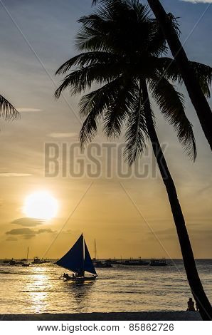 Sailing Boat Under Sail And Silhouette Of People Against A Beautiful Sunset