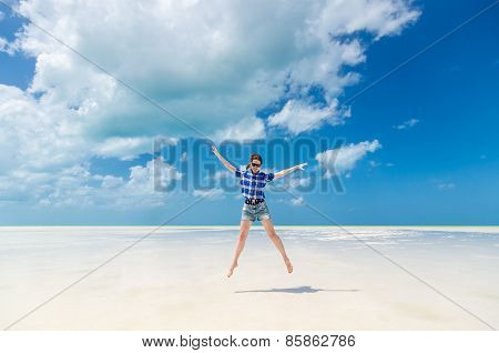 Cheerful Young Woman In Joy Jumping With Arms Out On Desert Sandy Lagoon Beach In The Caribbean