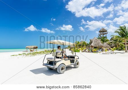 Young Man Driving Golf Cart Along Tropical Sandy Beach During His Caribbean Vacation