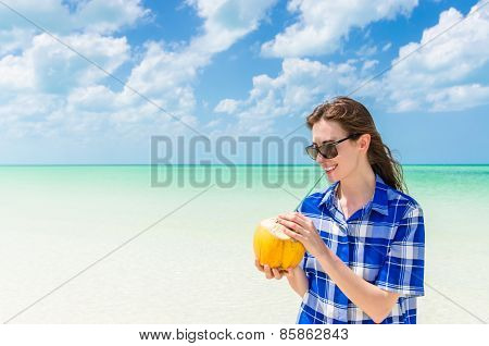 Young Cheerful Woman With Coconut Against Turquoise Sea At Tropical Sandy Beach During Caribbean Vac