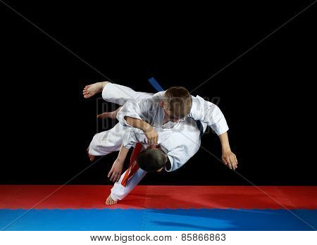Young athletes in the sharp drop perform judo throw
