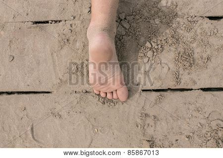 Toddler bare foot on wooden deck at the beach