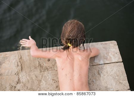 Little girl tanning on wooden deck at the lake on hot summer day