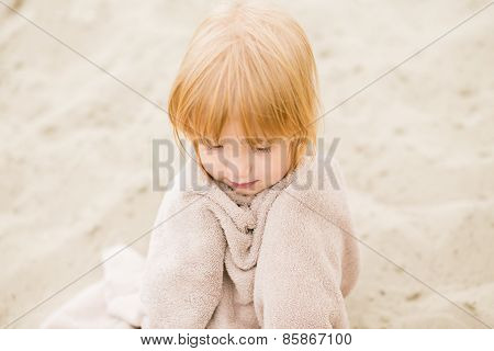 Little girl with red hair in a towel at the beach