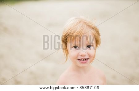 Toddler girl with red hair at the beach smiling at camera