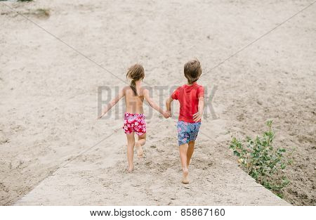 Fraternal twins run barefoot holding hands at the beach