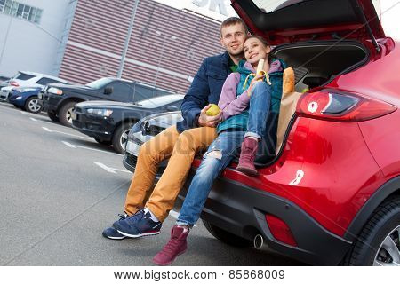 Young Couple Sitting At Car Trunk After Shopping