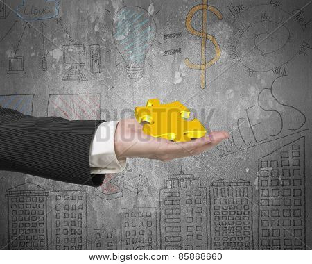 Hand Showing Gold Jigsaw Puzzle Piece With Business Concept Doodles