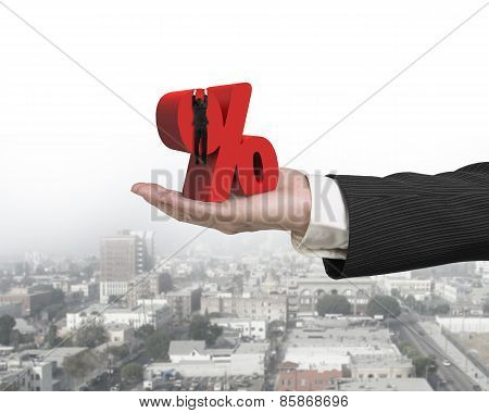 Hand Showing Businessman Hanging On Percentage Sign With Urban Scene