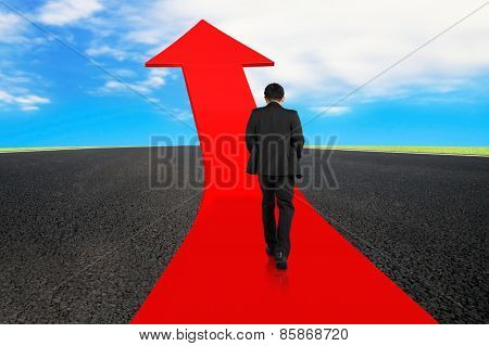 Businessman Walking On Arrow Road With Asphalt Pavement And Sky