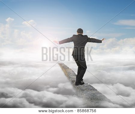 Businessman Balancing On Concrete Ridge With Sky Sunlight Cloudscape
