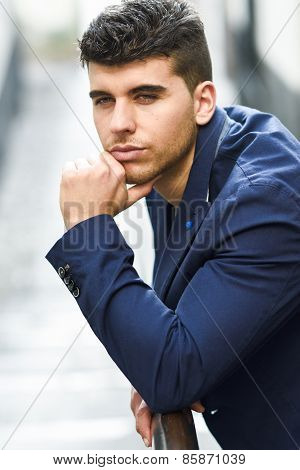 Handsome Young Man With Blue Eyes Posing Near A Wall