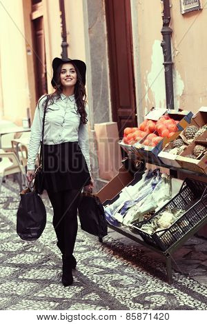 Young Woman With Shopping Bags In Urban Background
