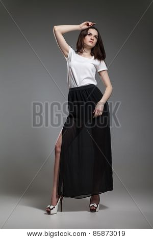 Beautiful model in white top and black skirt posing on grey background