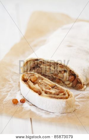 A Piece Of Apple Strudel On Baking Paper On A Light  Background