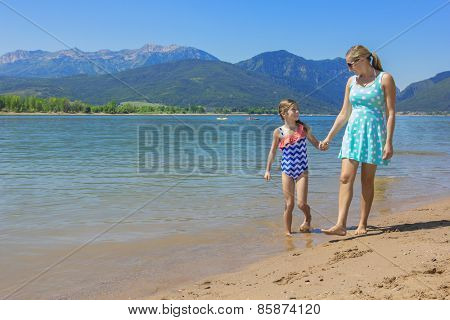 Mother and daughter walking together at scenic lake