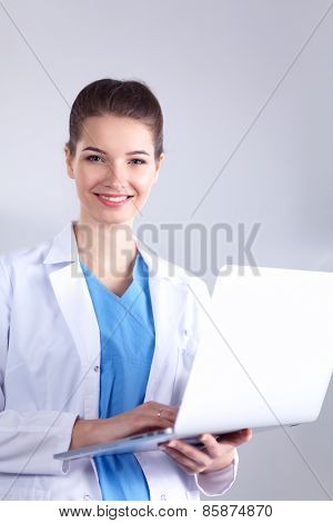 Portrait of young woman doctor in blue coat standing