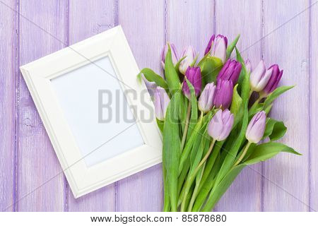 Purple tulip bouquet and blank photo frame. Top view over wooden table