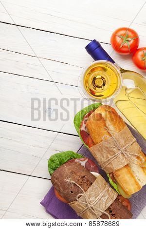 Two sandwiches with salad, ham, cheese and tomatoes with white wine on wooden table. Top view with copy space