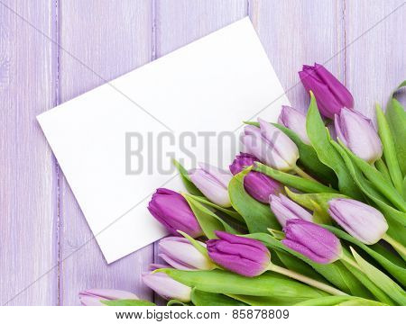 Purple tulip bouquet and blank greeting card. Top view over wooden table