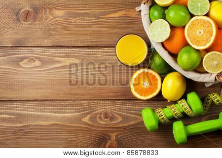 Citrus fruits in basket and dumbells. Oranges, limes and lemons. Over wood table background with copy space
