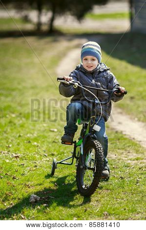 Little Boy Riding A Bicycle In The Park
