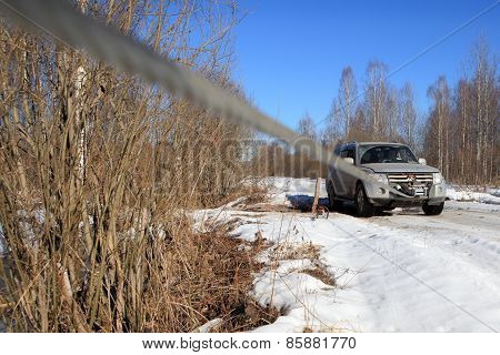 Icy Road In  Woods, Rope Extends From Winch Stuck Car.