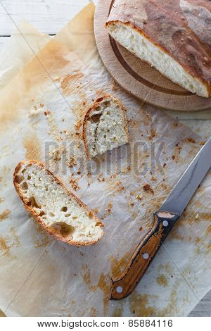 Sliced loaf of homemade bread on baking paper