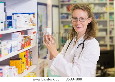Smiling pharmacist taking jar from shelf in the pharmacy