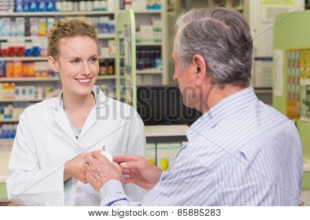 Pharmacist explaining something to a customer in the pharmacy
