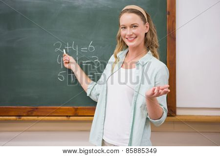 Teacher explaining maths in blackboard at elementary school