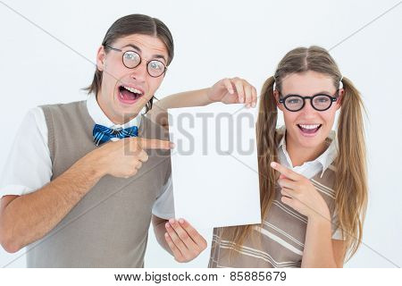 Geeky hipsters pointing at poster on white background