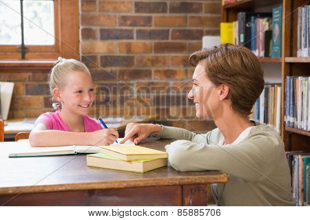 Teacher helping pupil in library at elementary school