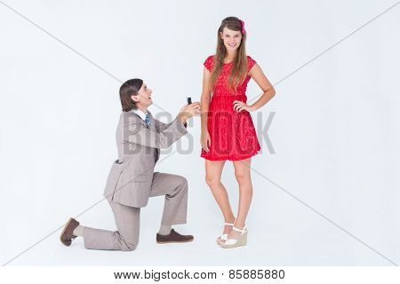 Hipster on bended knee doing a marriage proposal to his girlfriend on white background