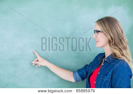 Smiling geeky teacher pointing the blackboard in classroom
